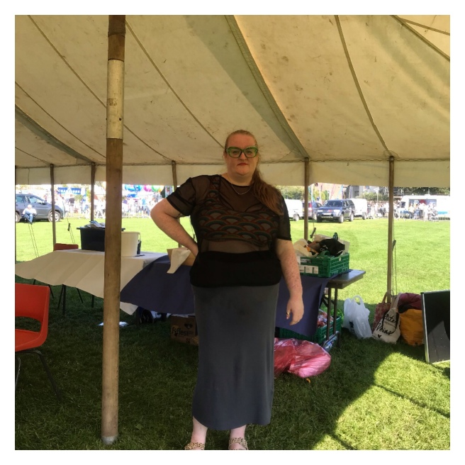 Plus size woman in tent wearing maxi skirt & rainbow crop top