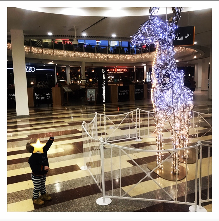 Toddler pointing up a big Xmas reindeer