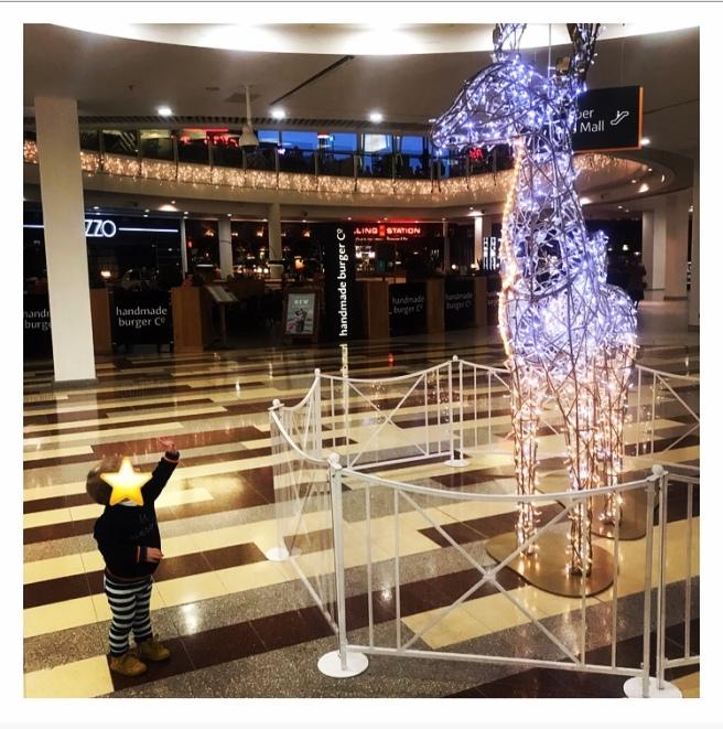Toddler pointing up a big Xmas reindeer