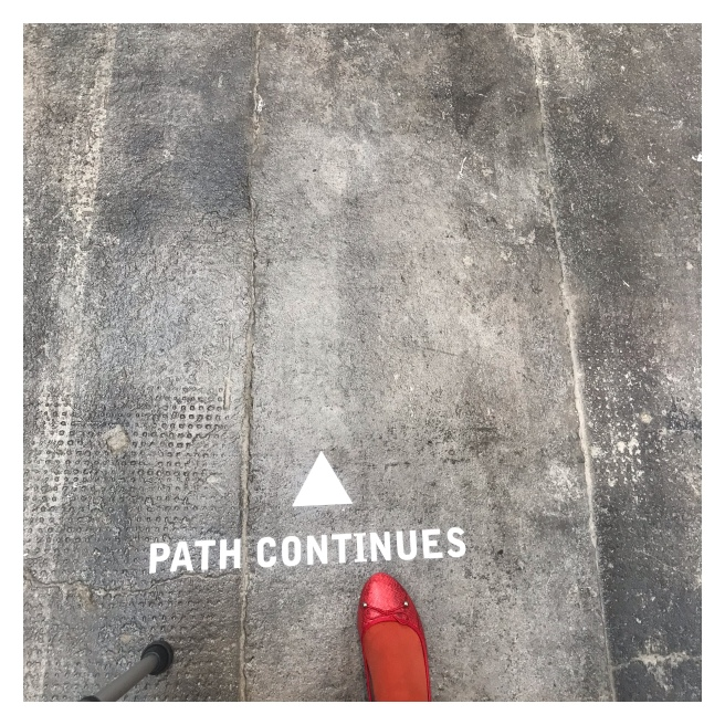 Path continued painted cement ground with foot & walking stick