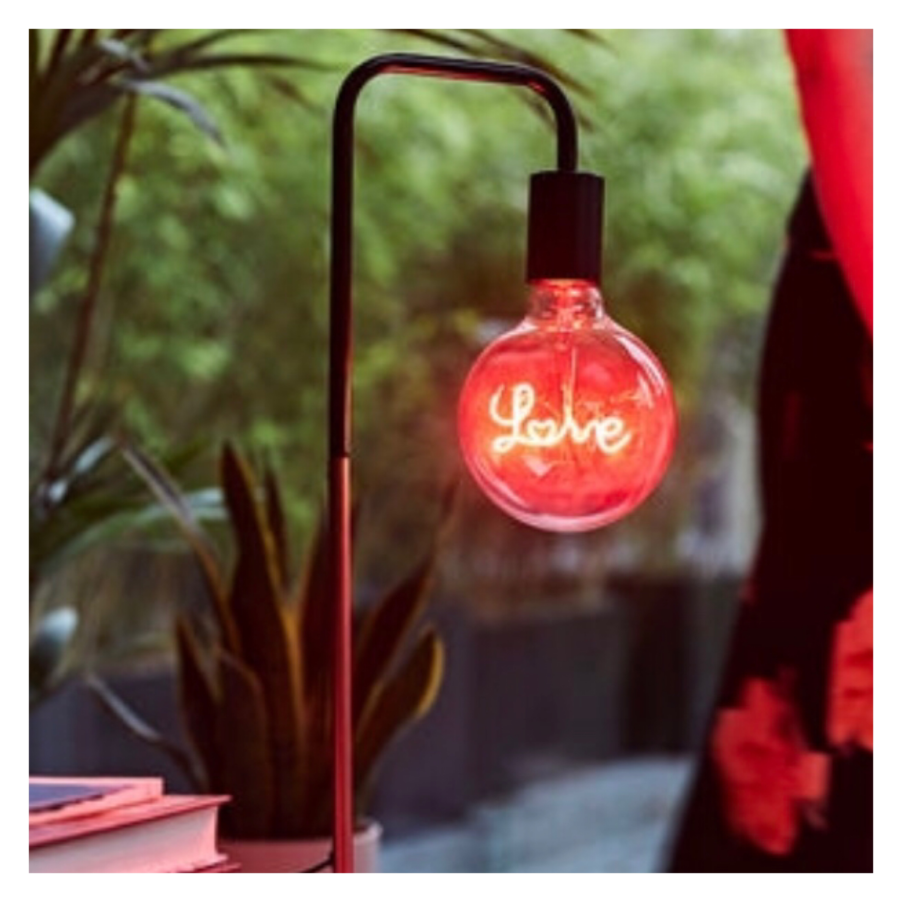 Desk last lamp with red neon 'love' inside large exposed bulb