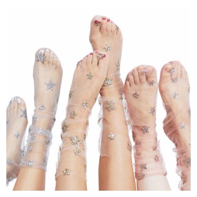 Three pairs of feet in tulle socks with metallic stars