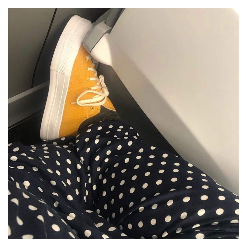 Woman's legs wearing polka dot trs & yellow converse