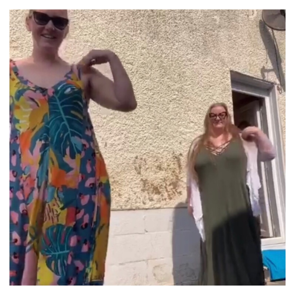 Two women doing tik tok dance on summer dresses