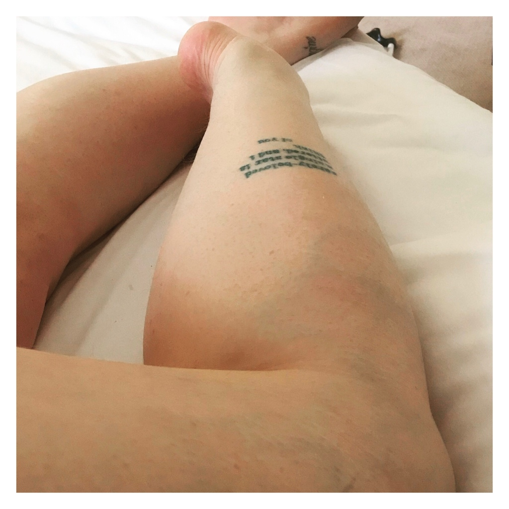 Pale legs with green tattoo lying in bed