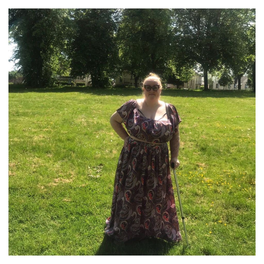 Plus size women wearing paisley print skirt  &  crop top in a park