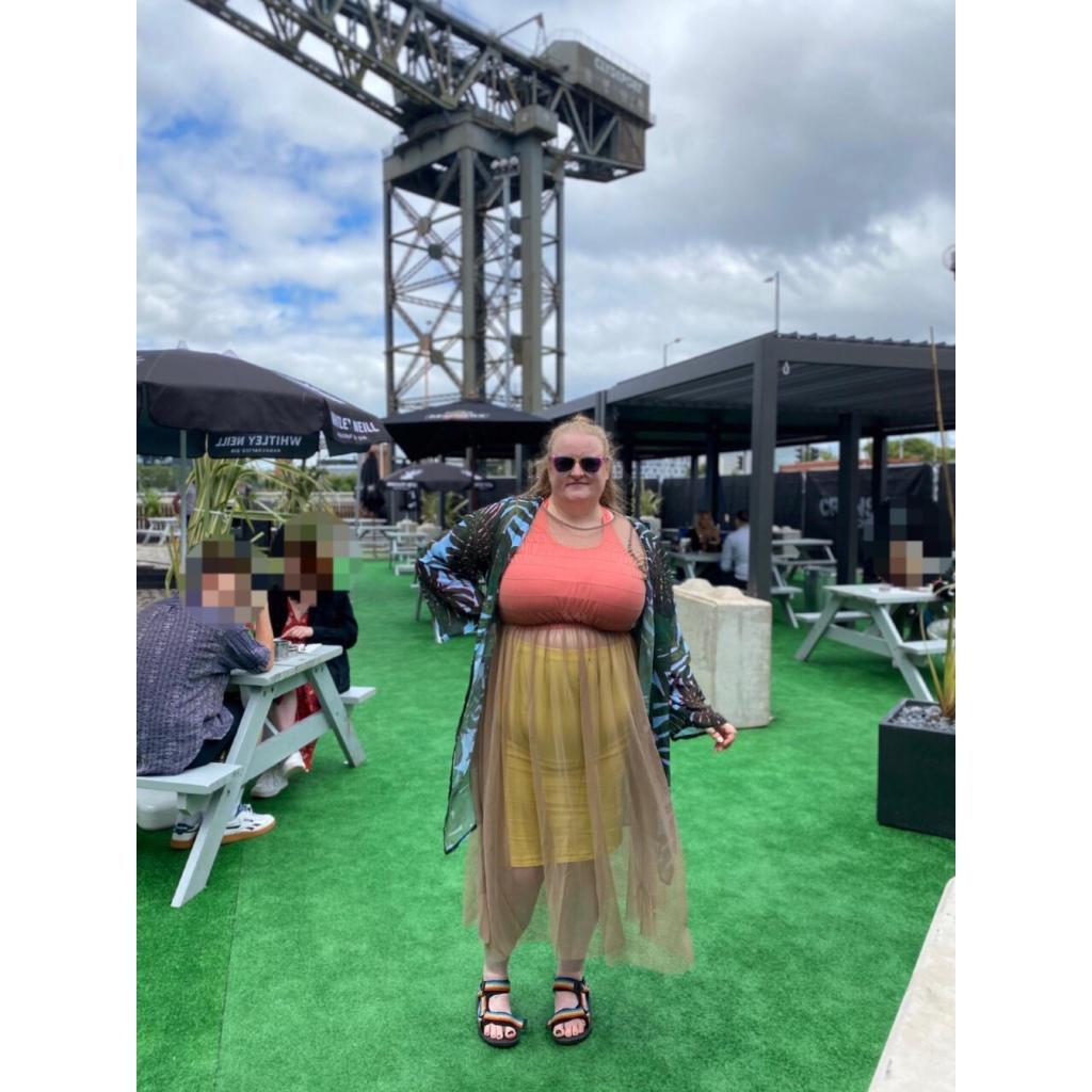 Plus size woman in beer garden wearing sheer dress with yellow skirt & crop top underneath