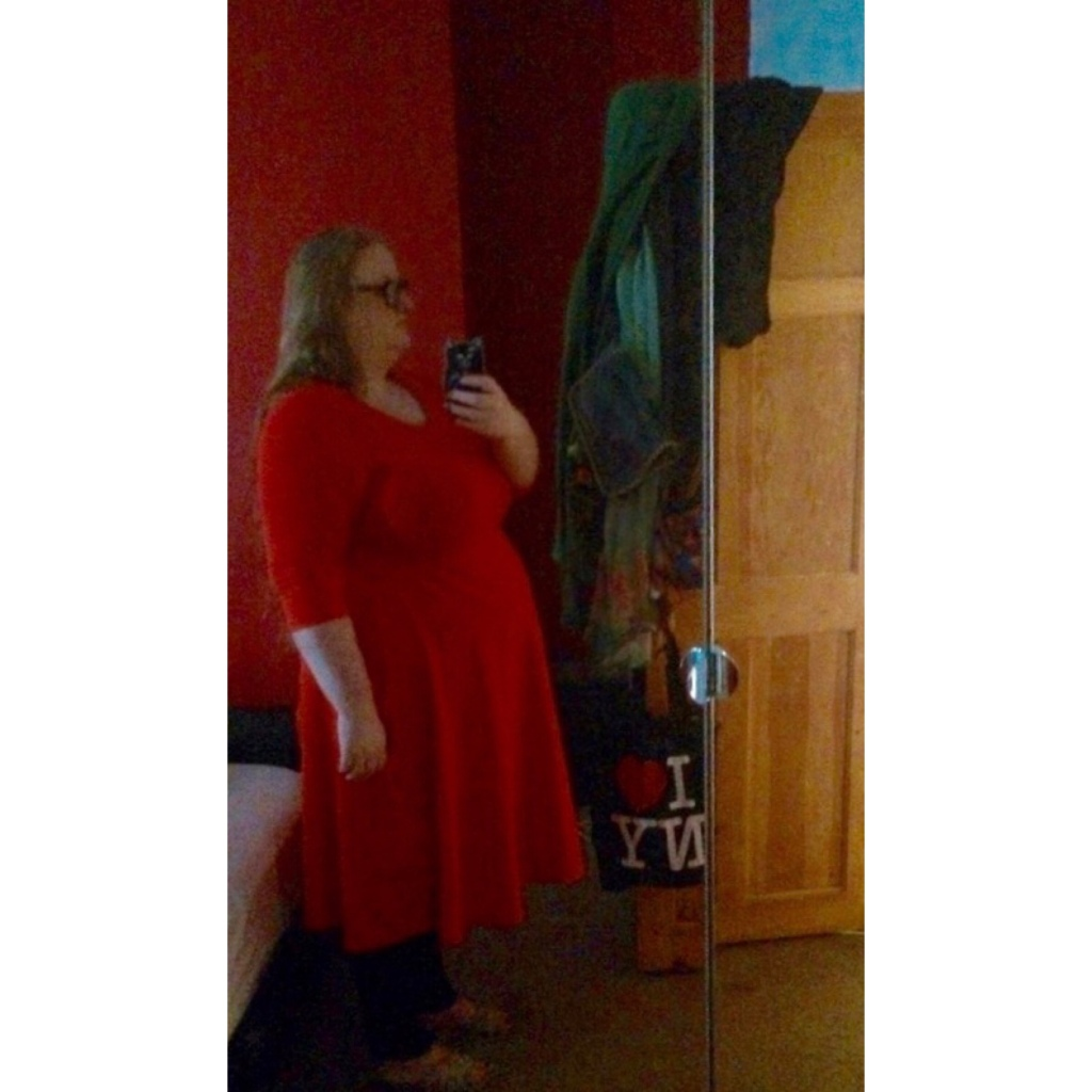 ly is wearing a red dress and taking a side on mirror selfie