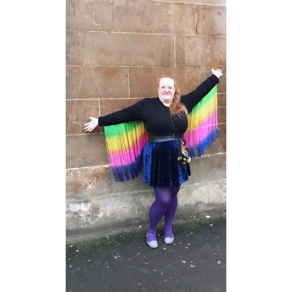 ly is standing against a sandstone building arms stretched out wearing rainbow fringed top & blue velvet skirt