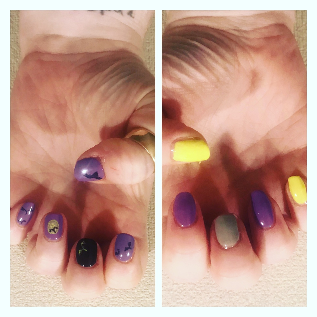 Halloween manicure with bat silohoutres against purple skies