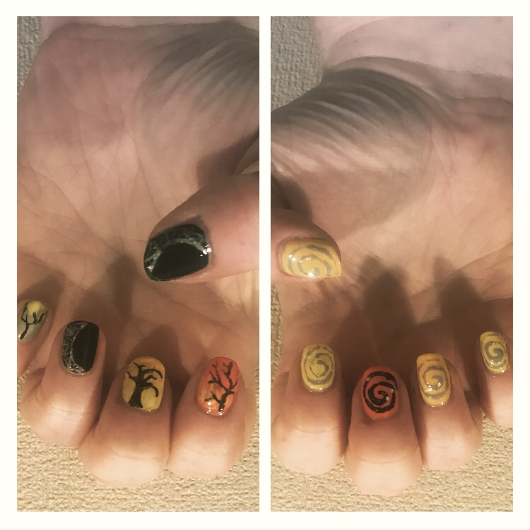 Halloween nail art with spooky trees and spider webs.
