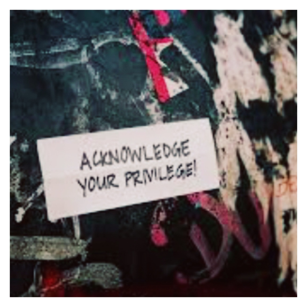 Graffitied wall with poster saying 'acknowledge your privilege '
