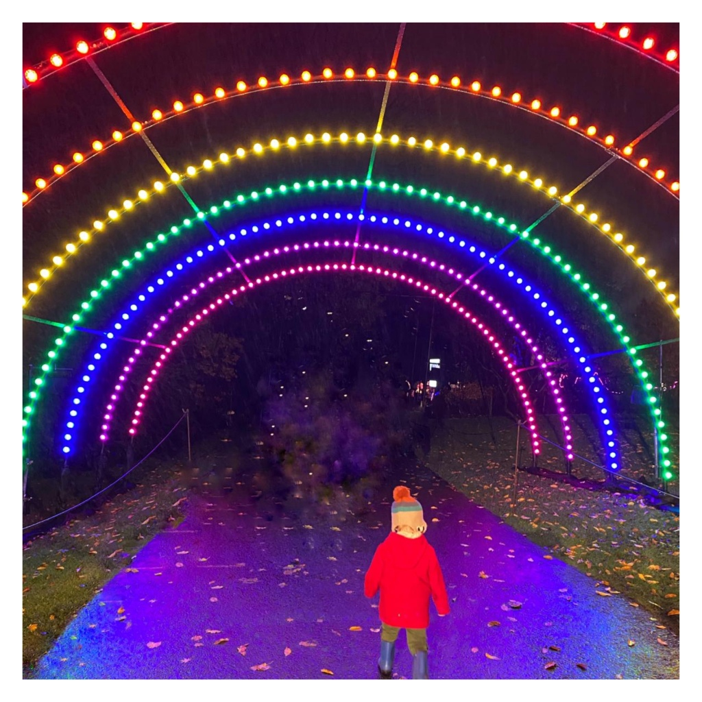 Toddler running under neon rainbow