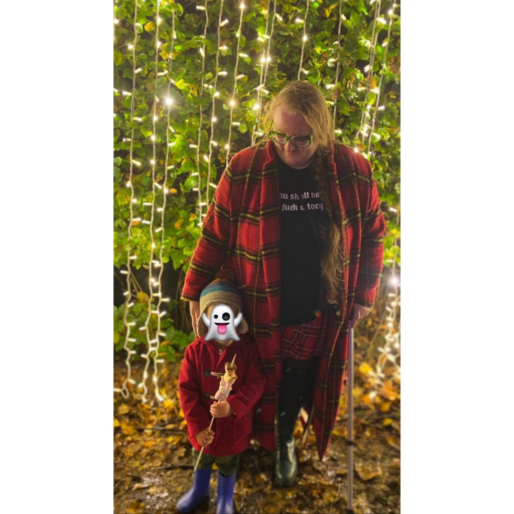 plus size woman in tartan coat with toddler in red duffle stunting infront of twinkly light wall