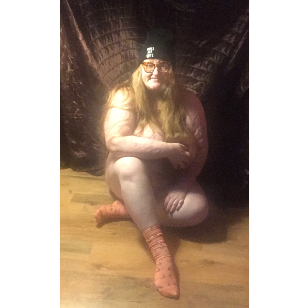 Plus sizesd naked women sitting on floor one arm across her breasts and one leg crossed to cover pubic area.Wearing a hat & socks