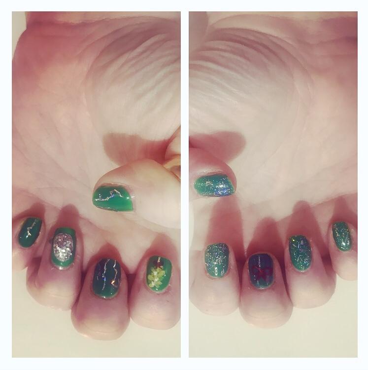 Xmas nail art.   Glitter ball and mistletoe on green background