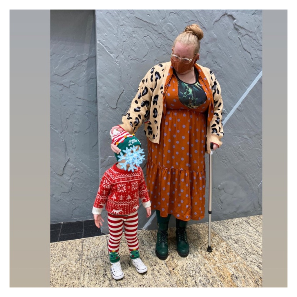 Ly wearing polka dot dress, leopard print cardi &  face mask with toddler in elf outfit