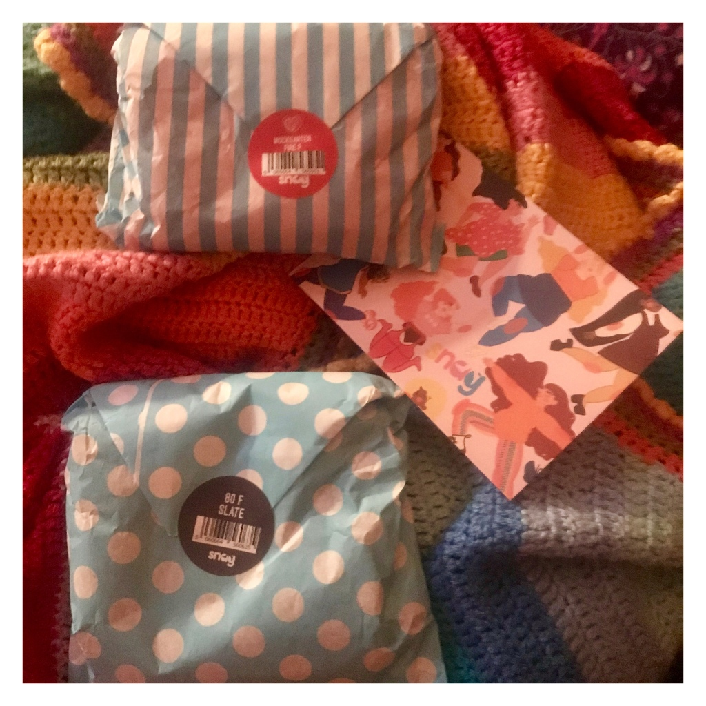 Two  little parcels wrapped in blue paper with snag tights card on a rainbow blanket