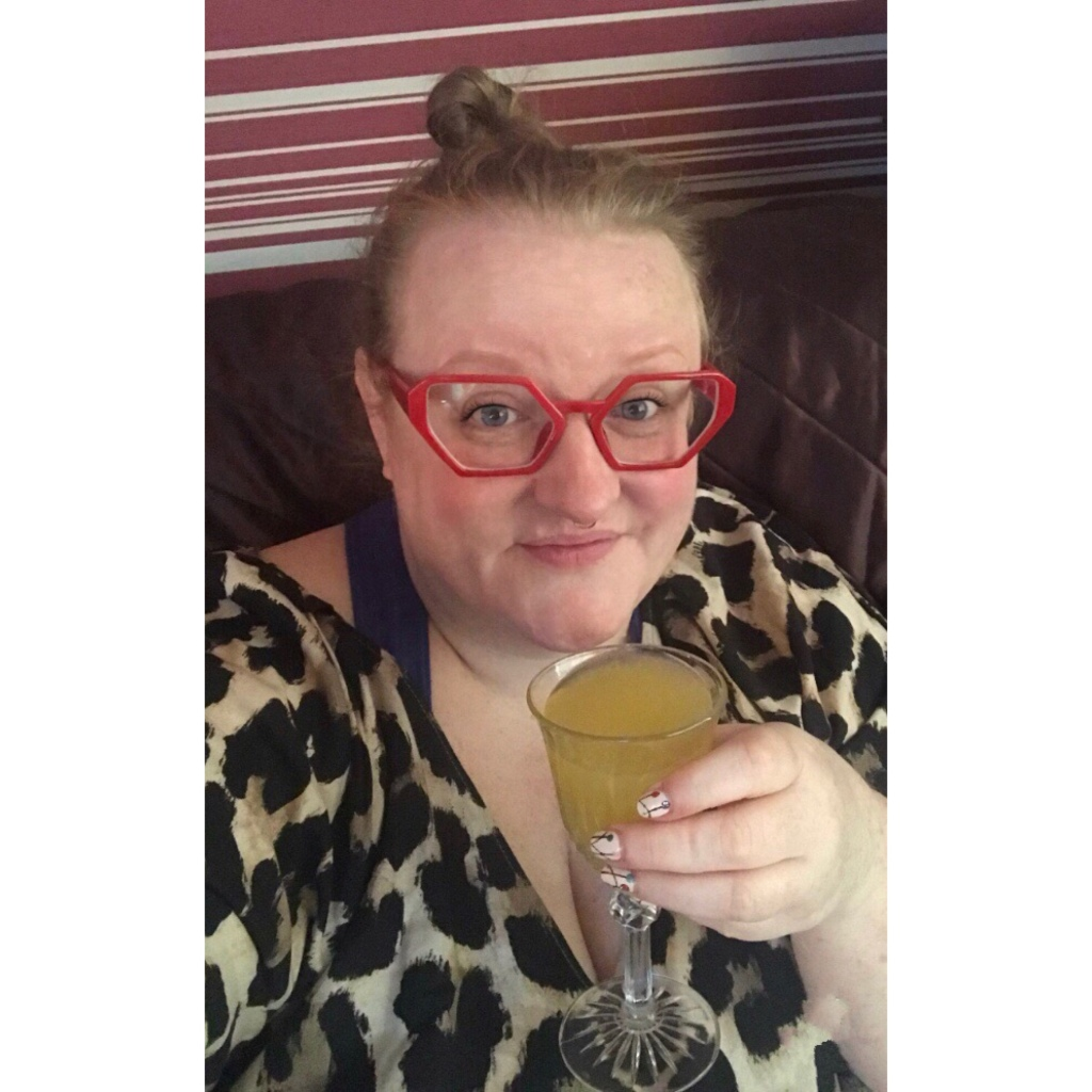 ly is wearing red glasses & leopard print. She is cheersing with a glass of bucksfizz