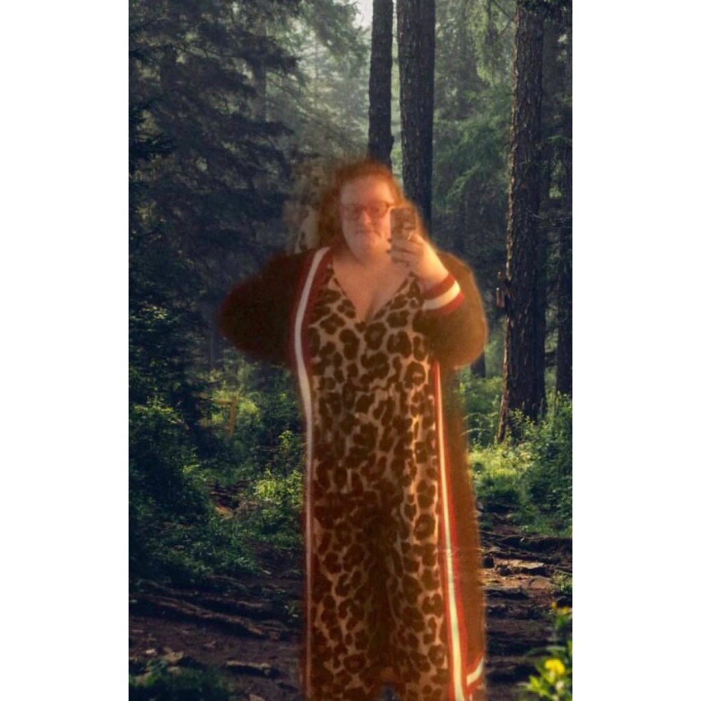 ly is  wearing leopard print jumpsuit & navy maxi cardi. The photo had Forrest background superimposed