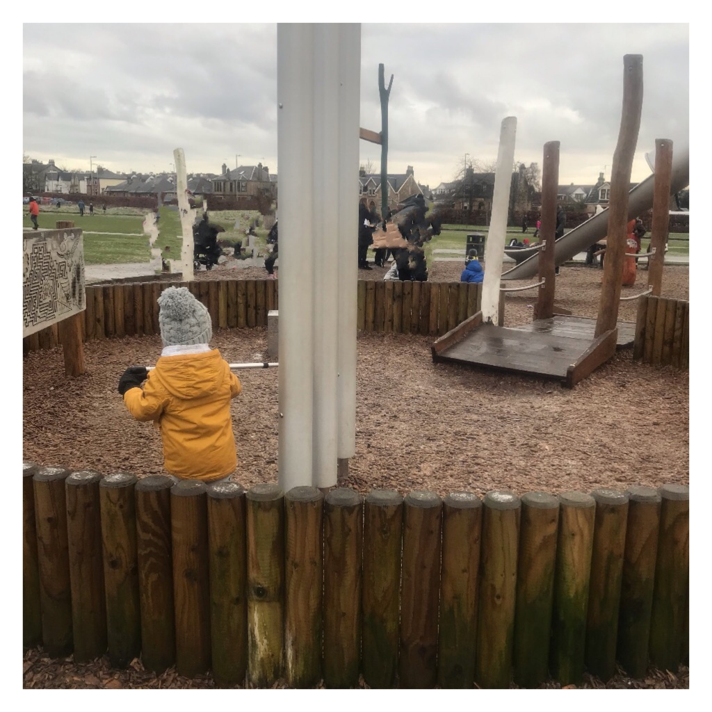 Toddler in coat & Woolly hat in playpark