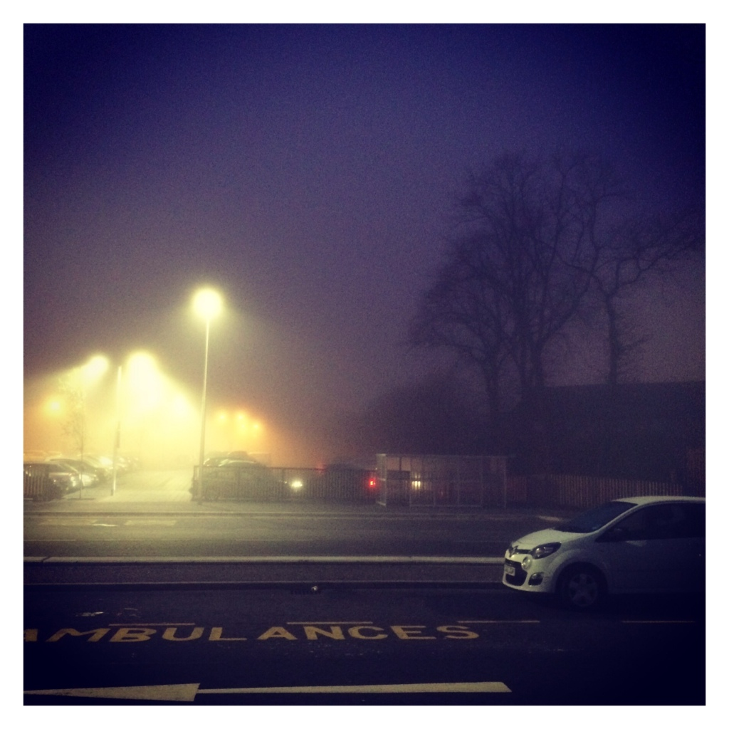 Foggy picture of cars outside hospital. Words ambulance only painted on ground