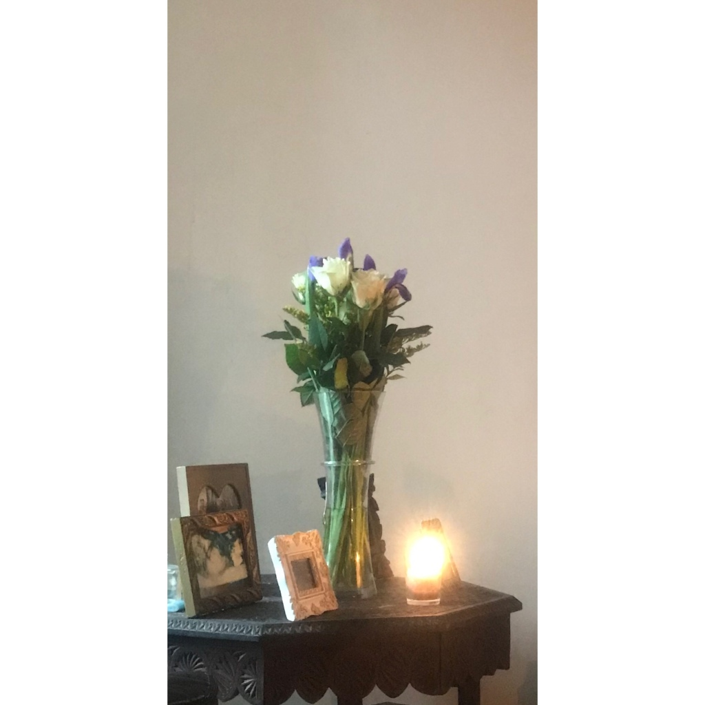 White roses in a vase, candles, photo frames on decorative table