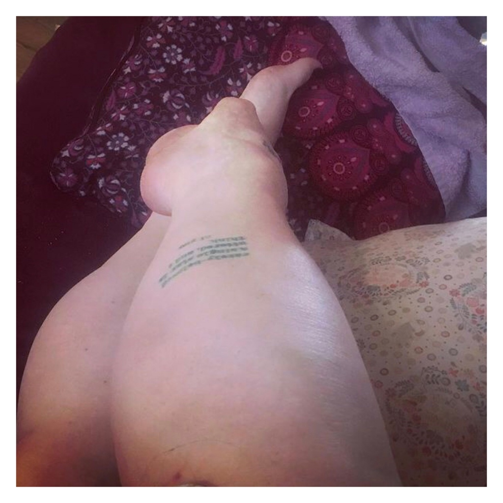 Pale white legs with green words tattooed on calf