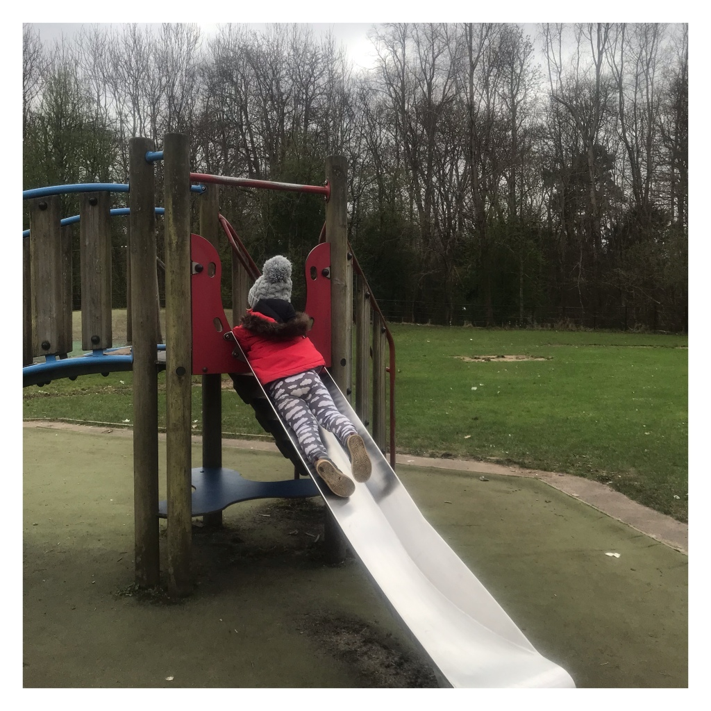 Toddler in cloud leggings going down a slide on his tummy