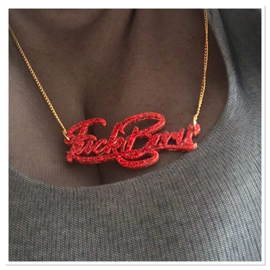 Red glitter text necklace  spelling 'fuck Boris'