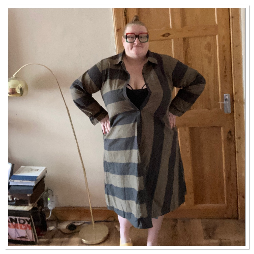 ly is standing by a brass floor wrap wearing a grey & green striped shirt dress and big square red & green glasses