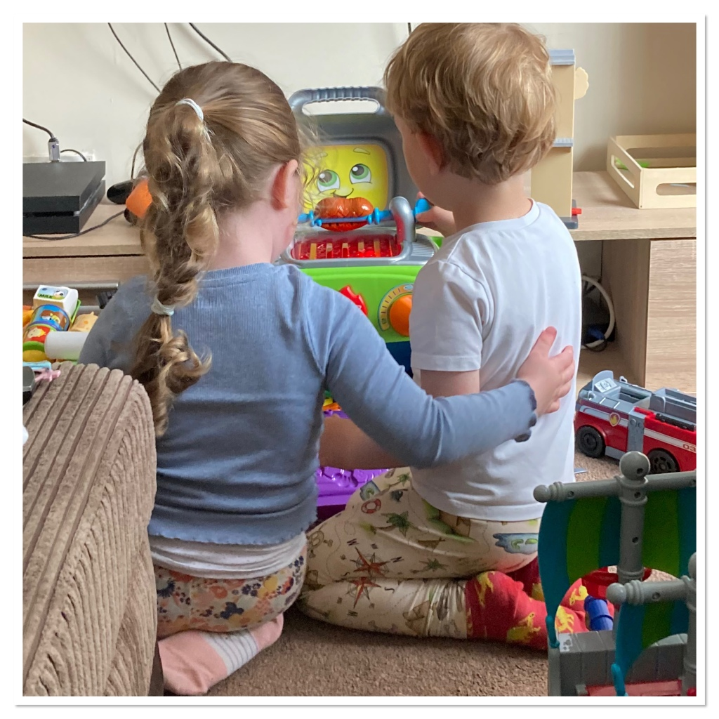 Two toddlers kneeling in floor  playing.  One with arm around the other