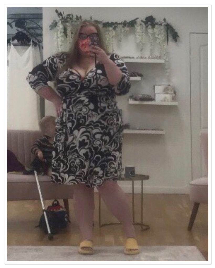 ly stands in front of s large silver mirror.  She is wearing a black & white dress with a pink face mask..
