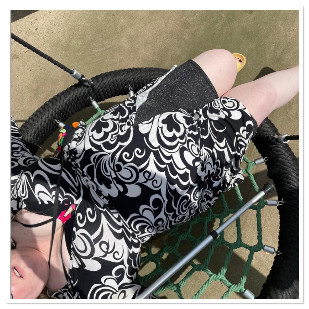 ly is lying in a large circular swing wearing a black and white dress