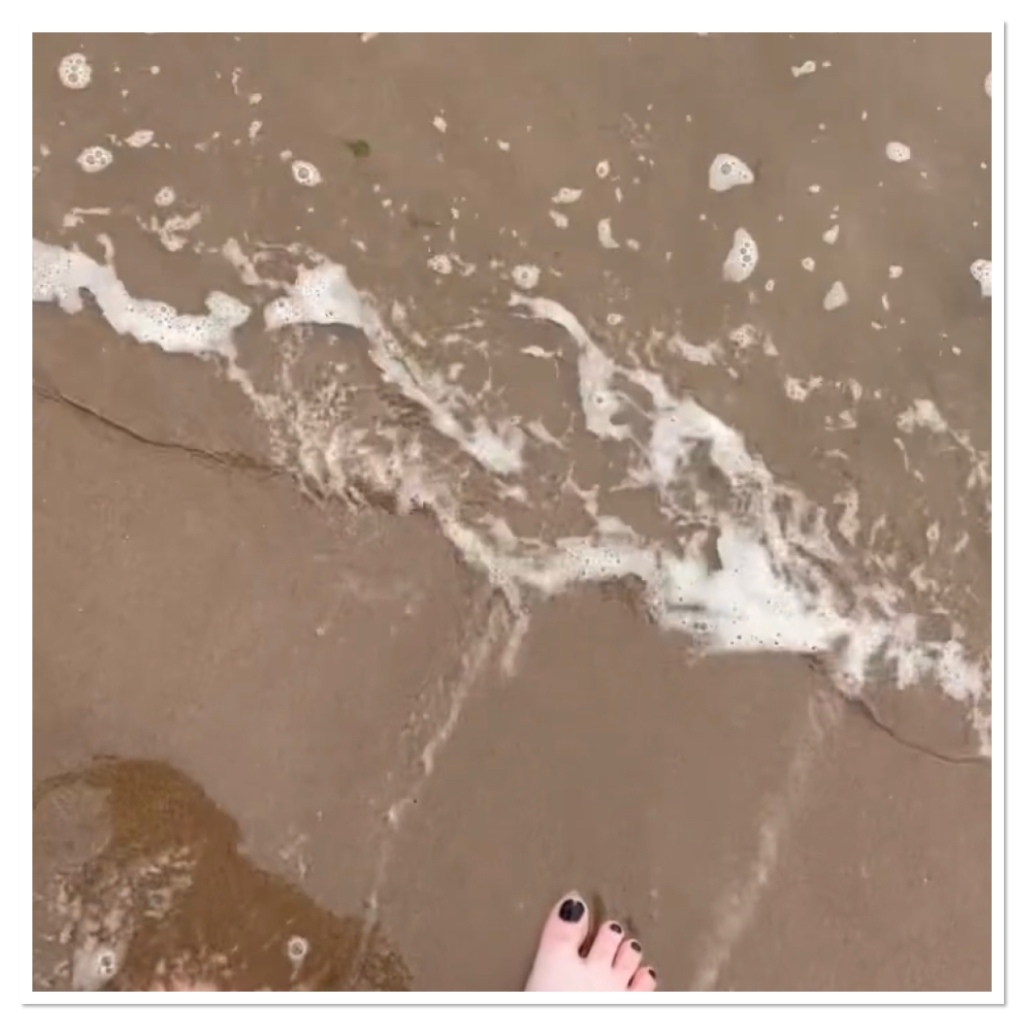 Foot with black painted tie nails on the sand with wave approaching