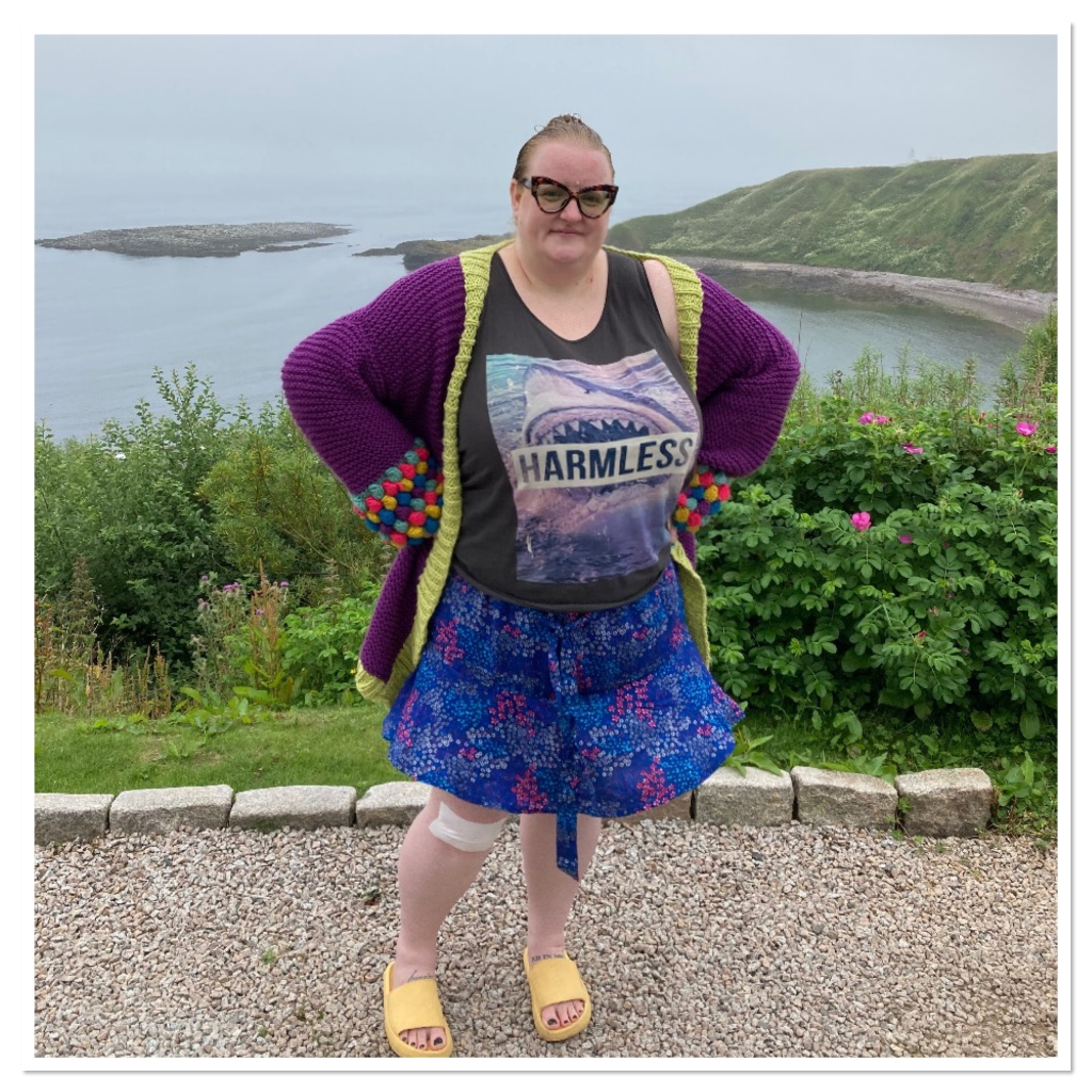 Ly is wearing floral mini skirt, shark vest & cardi and is standing above a pebble beaches bay