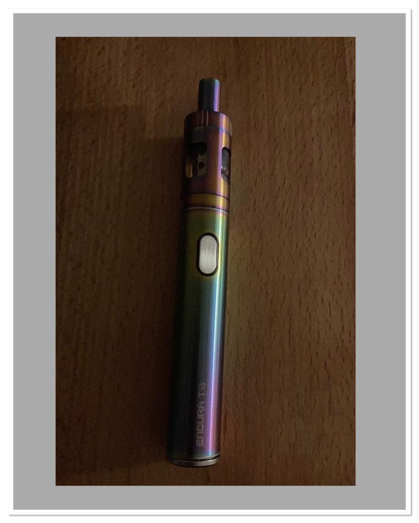 Multi coloured vape pen on wooden background