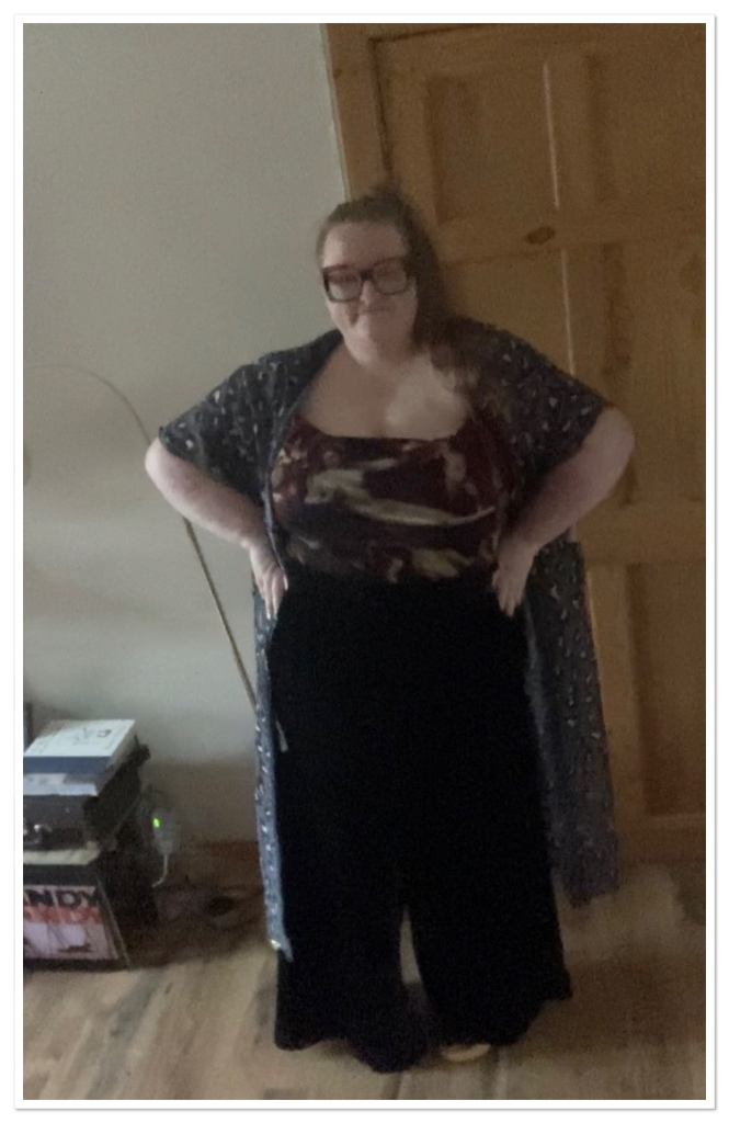 Ly is standing with her hands in her hips wearing black velvet trs, cherub print top & leopard print kimono