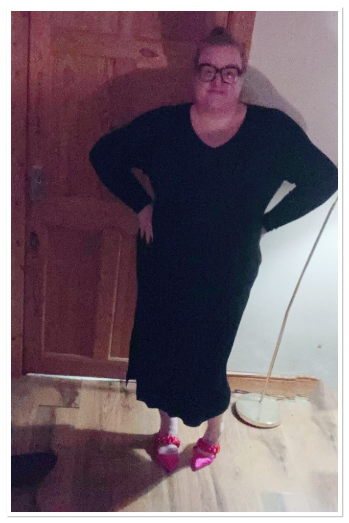 Ly is in her living room with her hands o her hips. She is wearing a calf length, v neck jumper dress