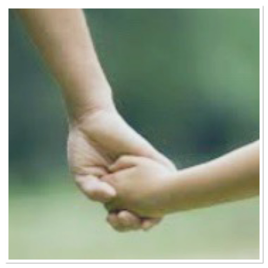 Adult hand holding a child's hand on green background